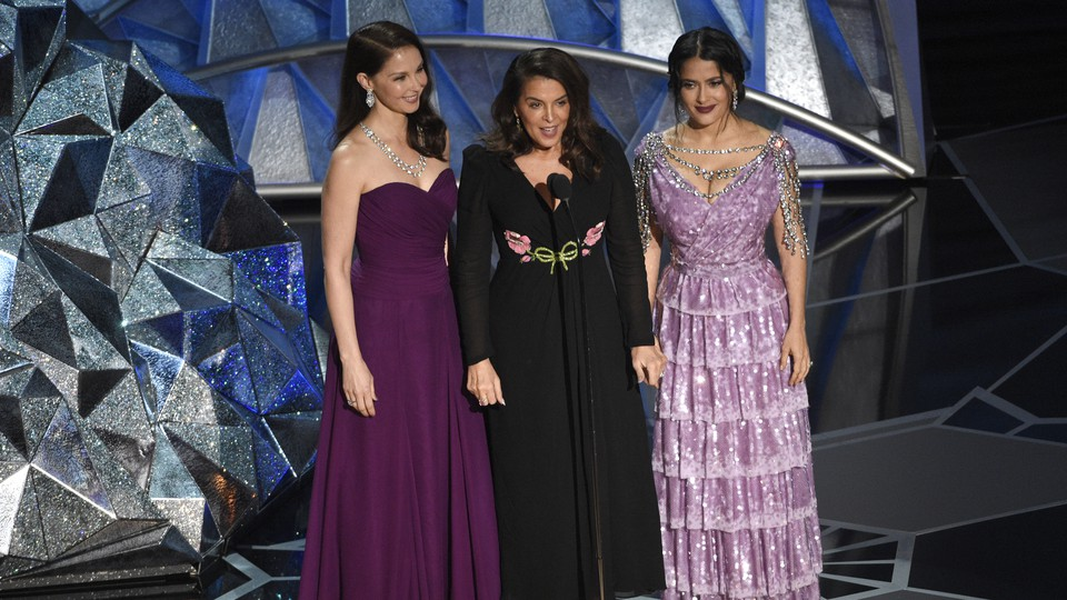 Ashley Judd, Annabella Sciorra, and Salma Hayek onstage at the 90th Academy Awards ceremony