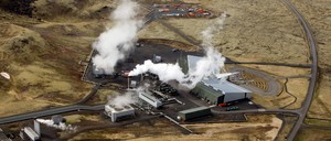 An aerial view of the Hellisheidi power station, with steam rising above brown fields