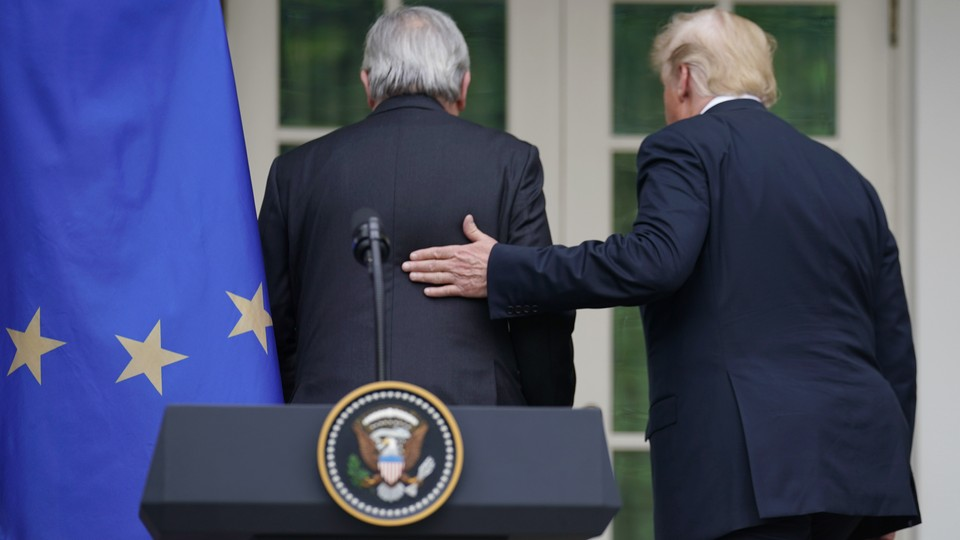 Trump places his hand on Juncker's back following a joint press conference at the White House Rose Garden.