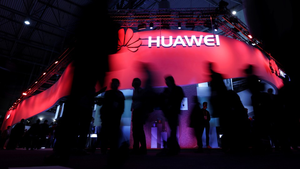 Visitors walk past a Huawei stand at the 2017 Mobile World Congress in Barcelona, Spain.