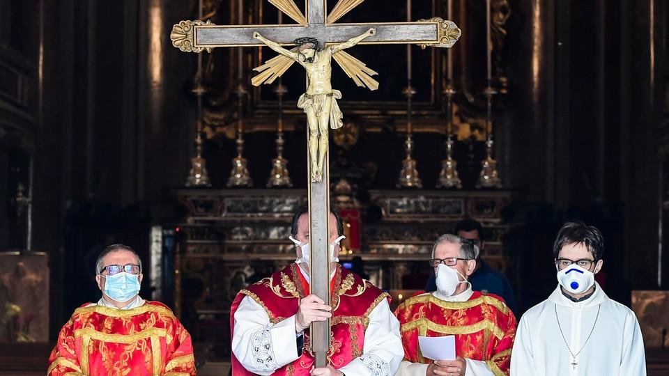 Parish priest wearing a face mask.