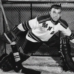 A hockey goalie shown from an earlier era has much smaller equipment than today's goalies