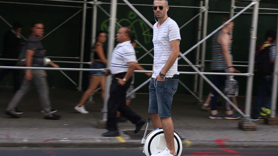 A person rides a one-wheeled hoverboard down a street.