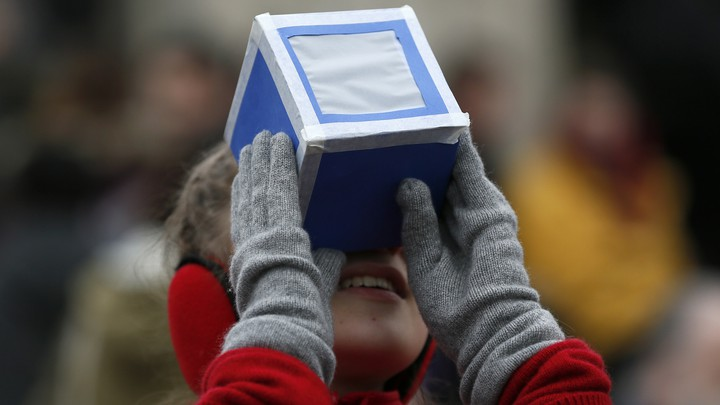 A girl looks through a viewing box.