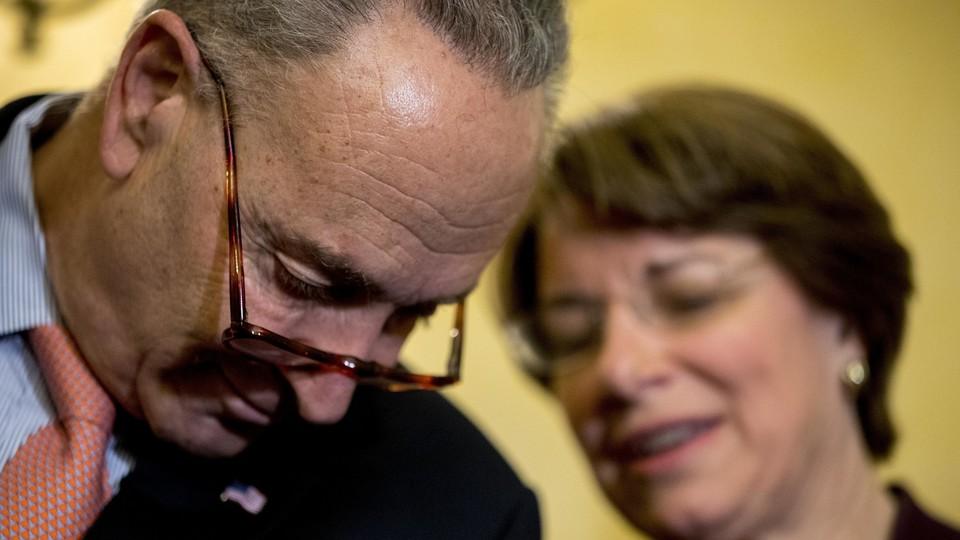 Senate Minority Leader Chuck Schumer and Senator Amy Klobuchar speak together during a news conference.
