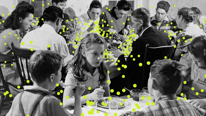 An illustration of people at a Thanksgiving table with droplets of the virus spreading from peoples' mouths.