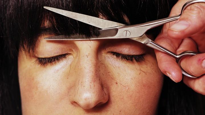 A woman getting her bangs cut