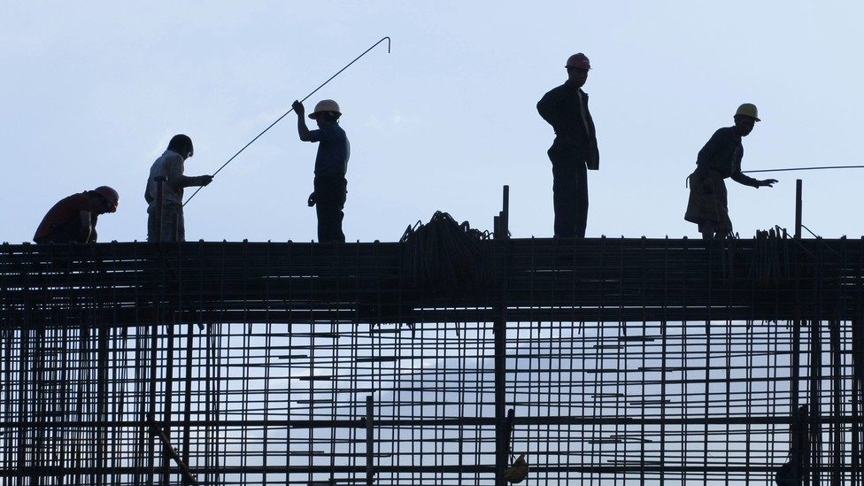 Silhouetted construction workers