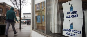 """A person walks past a storefront with a sign in the window reading """"We Are All One"""""""