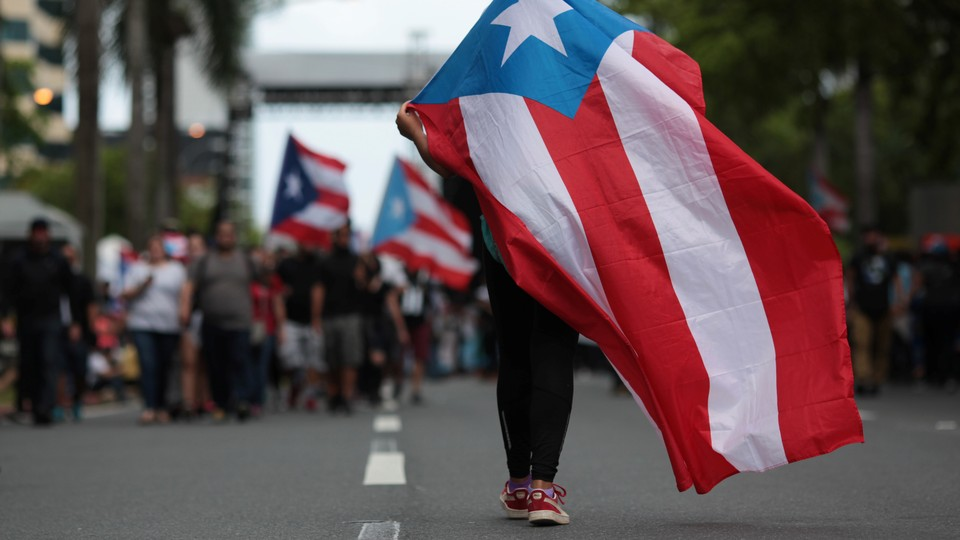 A Puerto Rican flag is waved during a protest against governmentausterity measures as the island faced a loomingdeadline to restructure its $70 billion debtin San Juan, Puerto Rico on May 1, 2017.