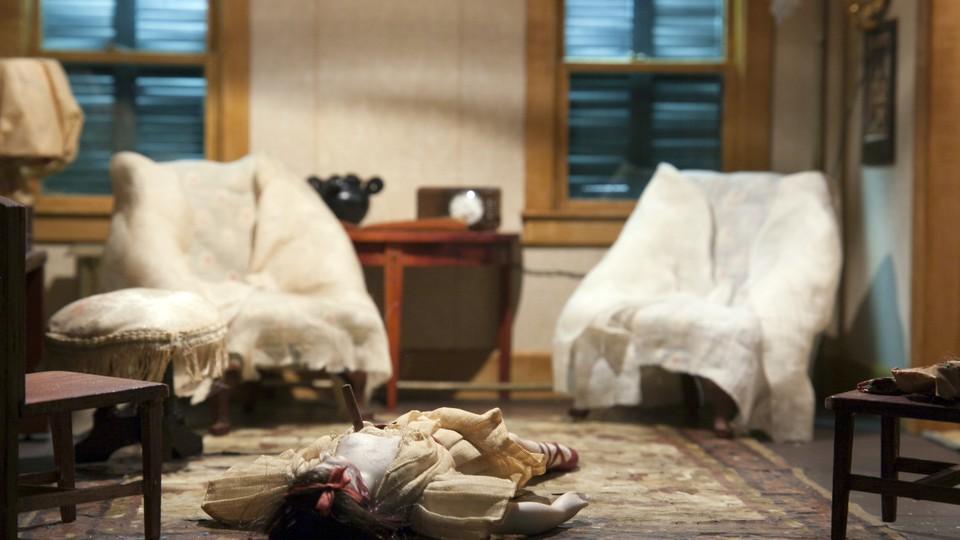 A diorama of a murder scene in a living room