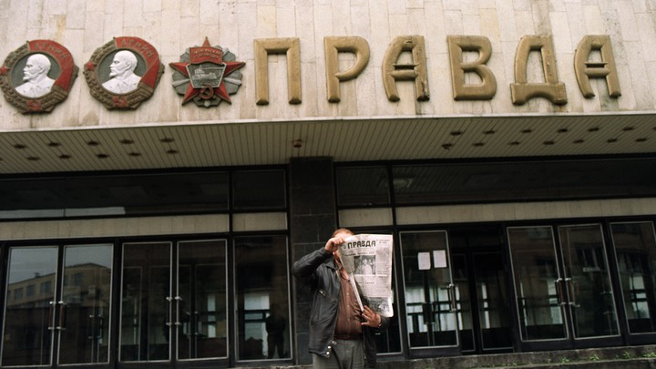 A man shows the headline of the 'Pravda' in front of the entrance of the building of the Soviet newspaper.