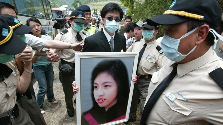 Burial of Dr Joanna Tse Yuen-Man who died of SARS at Gallant Garden, Wo Hop Shek. A relative is holding her portrait.