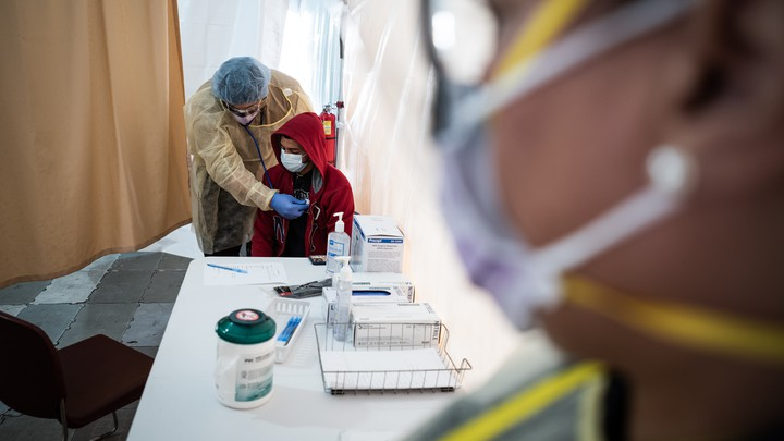 A doctor examines Juan Vasquez for a COVID-19 test inside a testing tent at St. Barnabas hospital on March 20, 2020 in New York City. St. Barnabas hospital in the Bronx set-up tents to triage possible COVID-19 patients outside before they enter the main Emergency department area.