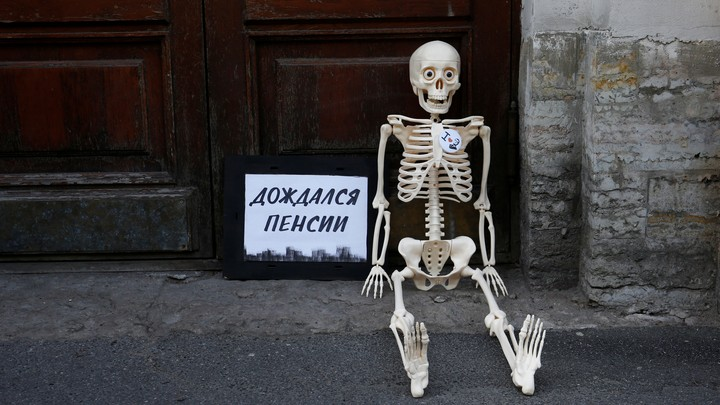 "During Russian protests against the raised retirement age, a fake skeleton is seated next to a sign that says, ""Waited for the pension."""