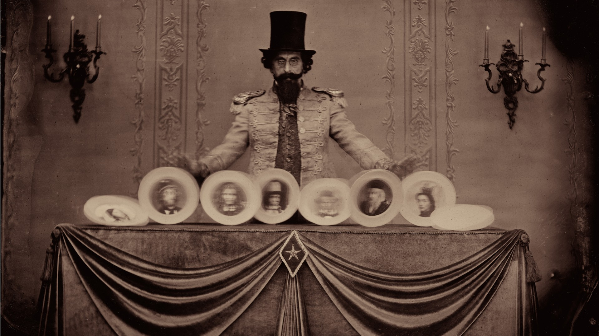 A man wearing a top hat is spinning plates