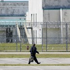 A guard crosses a prison parking lot.
