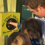 A man and two kids interact with the street perfume machine at an L.A. bus stop