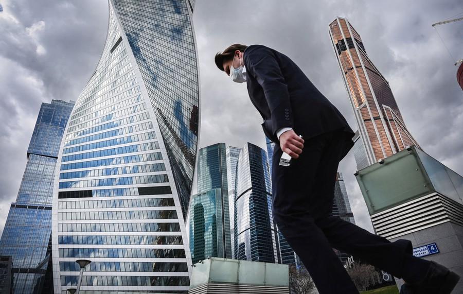 A man walks near distinctive skyscrapers.