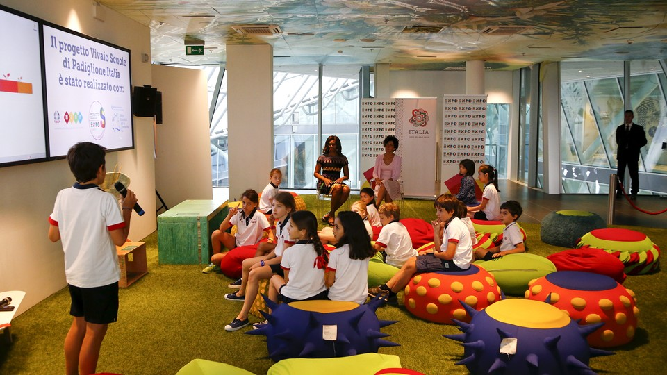 A group of elementary-school aged students sits on colorful chairs while looking at a powerpoint presentation. One boy holds a microphone and appears to be presenting.