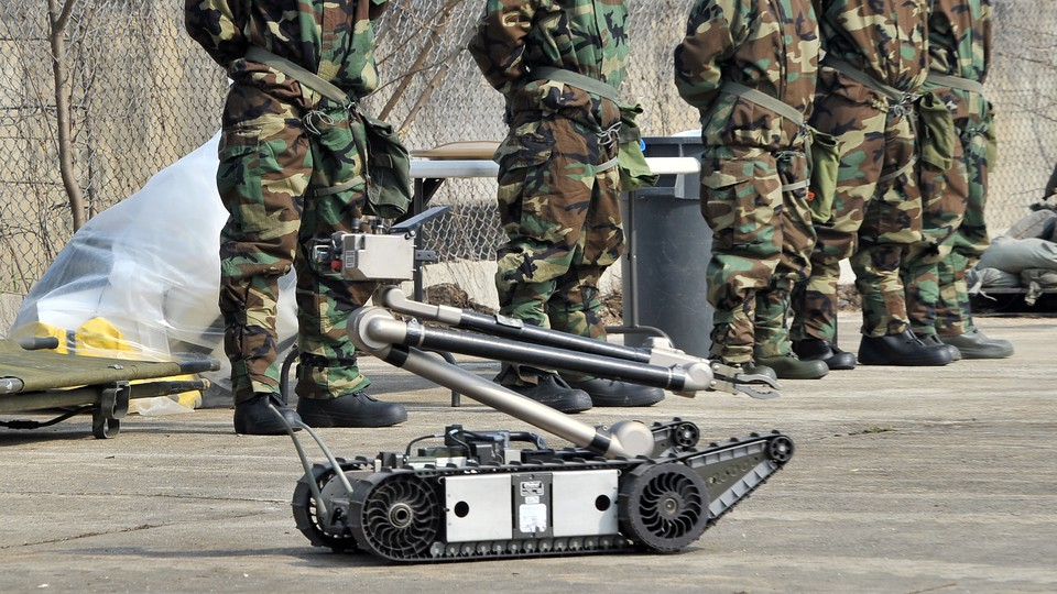 U.S. soldiers standing in uniform behind a black and silver robot