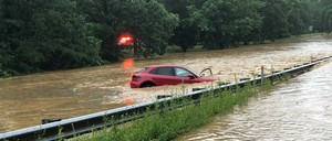 A car half-submerged in water on a roadway during a flash flood.