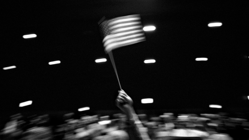 Black-and-white image of a person waving an American flag