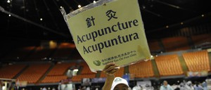 Volunteer Wen Hsien holds up a sign offering free acupuncture on the last day of a free health care clinic set up by Remote Area Medical in Inglewood, California.