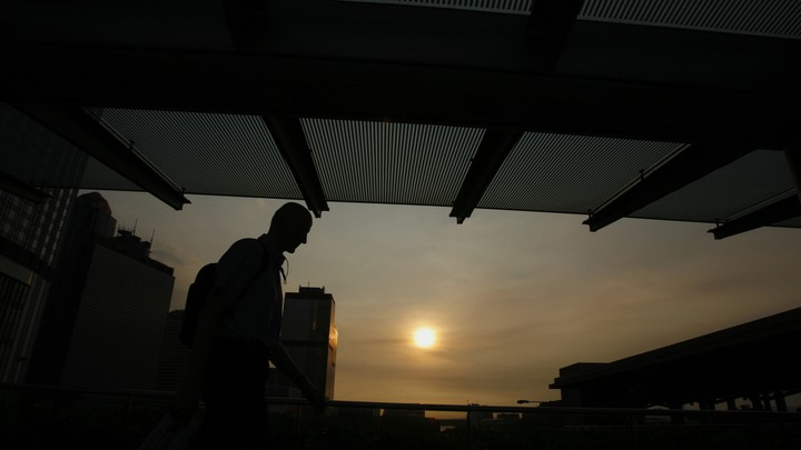 An expatriate business worker leaves an office building as the sun sets in Hong Kong's financial-business district on July 13, 2009.