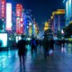 Blurred individuals walk on a street lit by colorful signs.