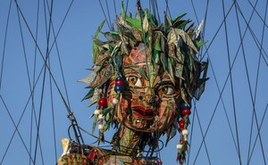 The head of a giant puppet is seen surrounded by cables.