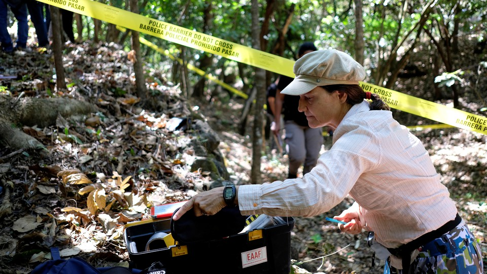 A member of the Argentine Forensic Anthropology Team works at the scene of the El Mozote massacre.