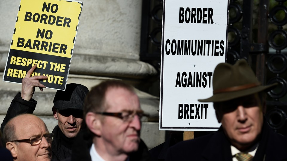"""Four protestors hold signs reading, """"No Border No Barrier, Respect the Remain Vote"""" and """"Border Communities Against Brexit."""""""
