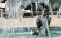 A man sits in a pool, looking bored