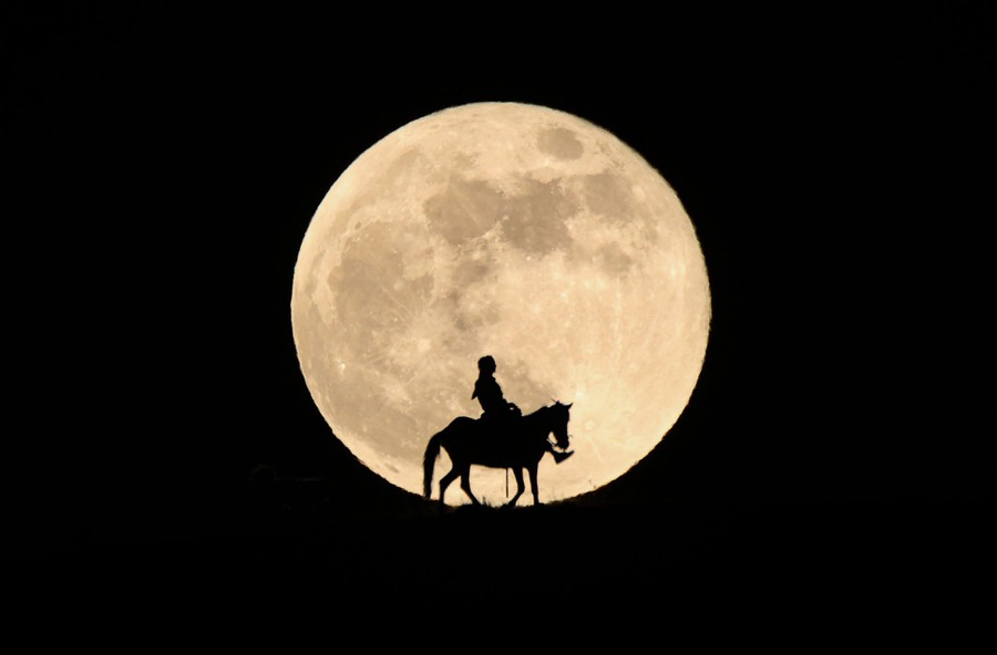 A person rides a horse in front of a full moon.