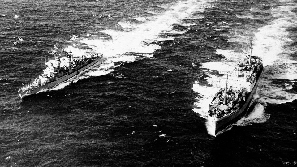The U.S. Destroyer, Barry, pulls alongside the Russian freighter, Anosov, to inspect cargo, in the Atlantic Ocean.