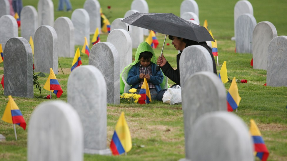 A child sits under an umbrella with an adult in a cemetery. Colombian flags are in the ground next to each headstone.