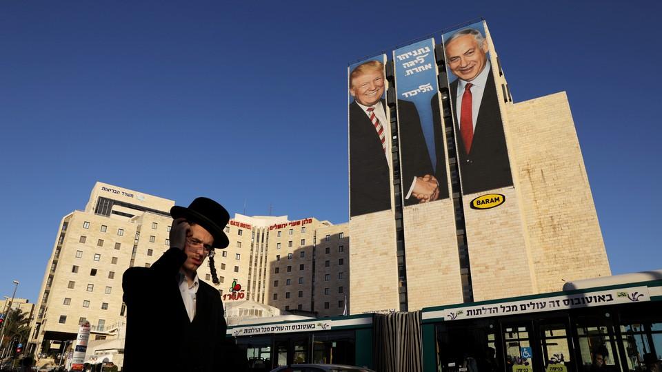 A man in Jerusalem walks past a Likud election-campaign billboard depicting President Donald Trump shaking hands with Israeli Prime Minister Benjamin Netanyahu.