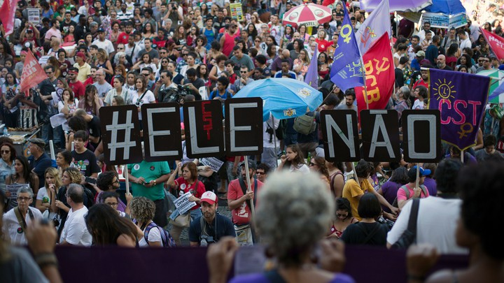 "Demonstrators protest in Rio de Janeiro days before Bolsonaro was elected. They told a large sign saying ""#EleNao,"" or ""#NotHim."""