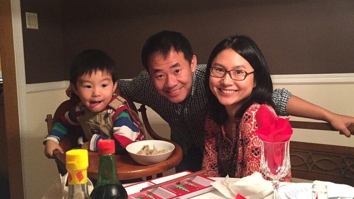 Xiyue Wang poses with his wife and young son at a dinner table.