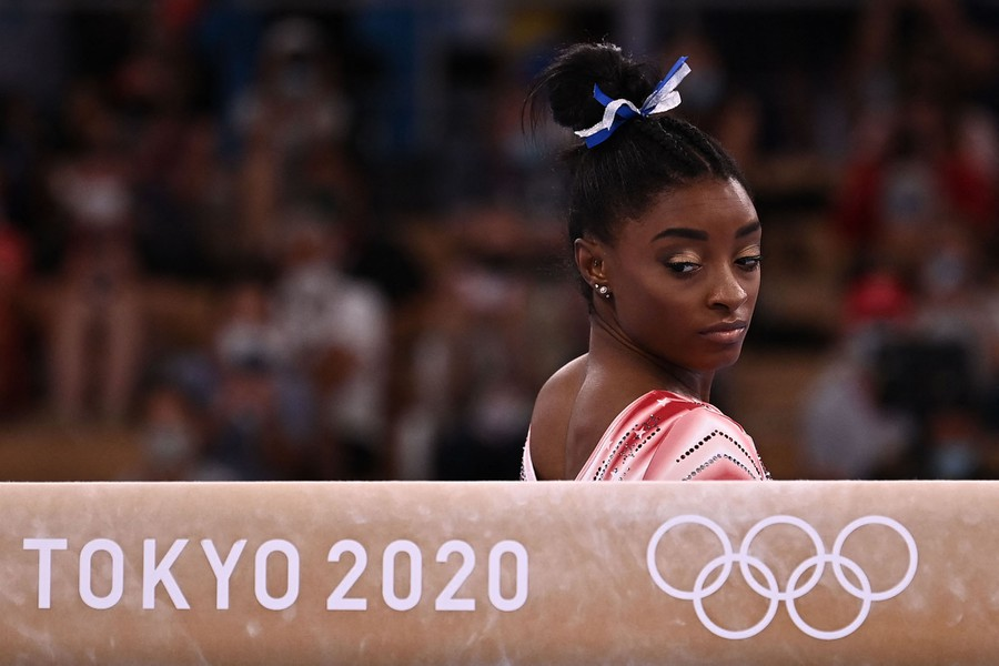 A gymnast looks over her shoulder at a balance beam.