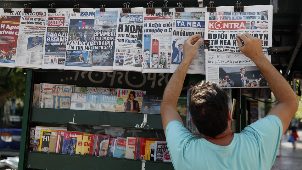 A vendor adjusts the front pages of the Greek newspapers, which refer to the election result