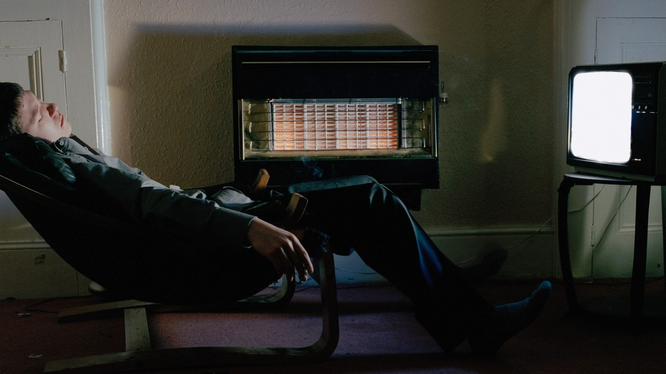 man sleeps in front of a TV