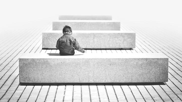A boy sits on a bench