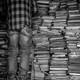 Man on ladder next to stacks of books