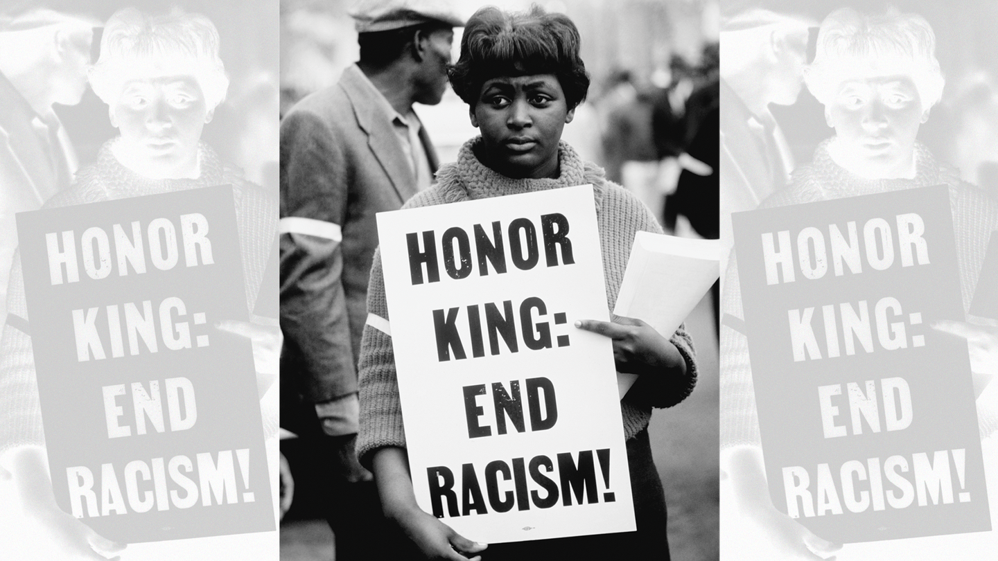 """woman holding sign """"Honor King: End Racism!"""""""