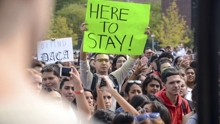 """A protester holds a sign that reads """"Here to Stay!"""""""