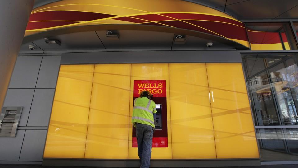 A man stands at a Wells Fargo ATM.