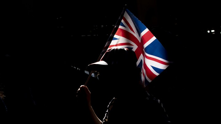 A silhouetted person holds up a Union Jack flag.
