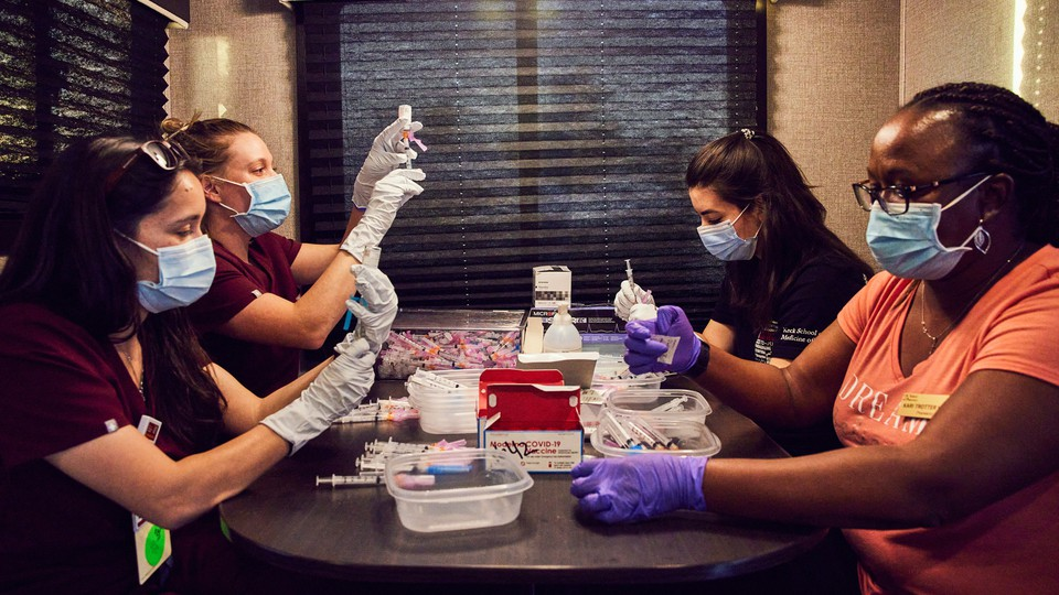 Four people sit filling vials with vaccine using syringes.